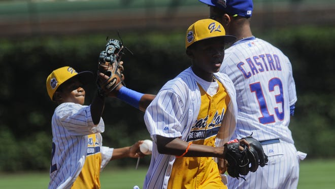 Cubs shortstop Starlin Castro high-fives members of the Jackie Robinson West Little League 2014 Champions in September.