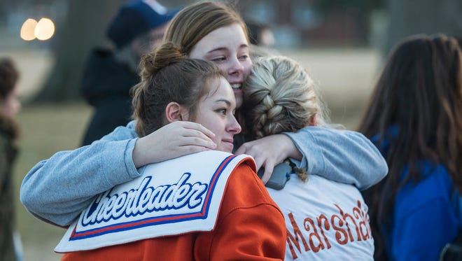 Alyssa Edging, center, a student at McCracken County High School, embraces Erica Johnson, left, and Abigail Hicks, both juniors at Marshall County High School in Benton, Ky., following a prayer vigil in Paducah on Jan. 24, 2018.