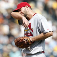 St. Louis pitcher Adam Wainwright wipes his brow after Pittsburgh loaded the bases during the fifth inning.