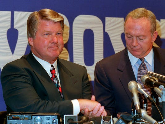 FILE - In this March 20, 1994, file photo, Jimmy Johnson, left, shakes hands with Dallas Cowboys owner Jerry Jones at a news conference in Irving, Texas, to announce that Johnson was leaving as coach of the Cowboys. Jones is to be inducted soon in the Pro Football Hall of Fame.(AP Photo/Ron Heflin, File)