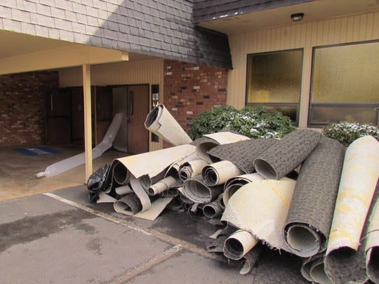Summit Cleaning and restoration crews pile up carpets and remove hazardous chemicals at Silverton Community Seventh-day Adventist Church, which was rendered temporarily unusable by vandalism this month.