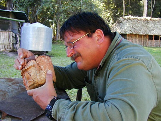 UCF professor, Arlen Chase, analyzes an artifact from