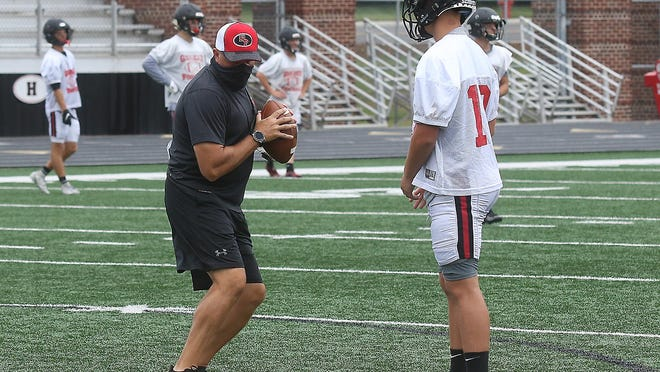 New Philadelphia head football coach Matt Dennison instructs some of the potential quarterbacks during the first day of practice Saturday at Woody Hayes Quaker Stadium.