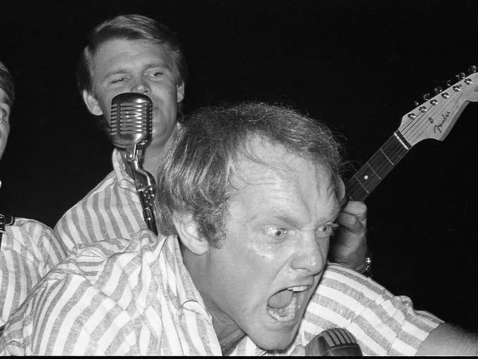 Beach Boys lead singer Mike Love snarls at the audience while, Glen Campbell sings background vocals. During a concert at Freedom Hall.  Dec. 28, 1964