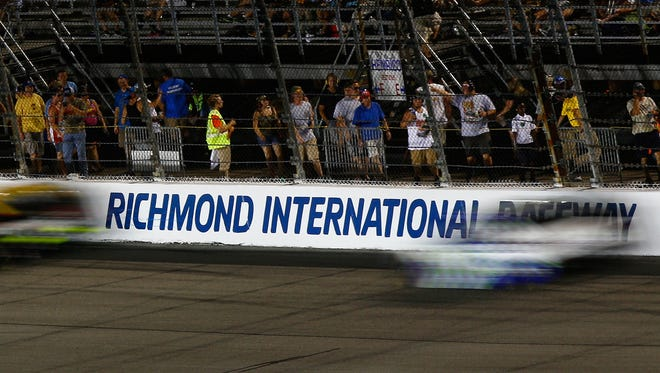 Fans crowd a fence as cars race during the  Federated Auto Parts 400 Saturday night at Richmond International Raceway.