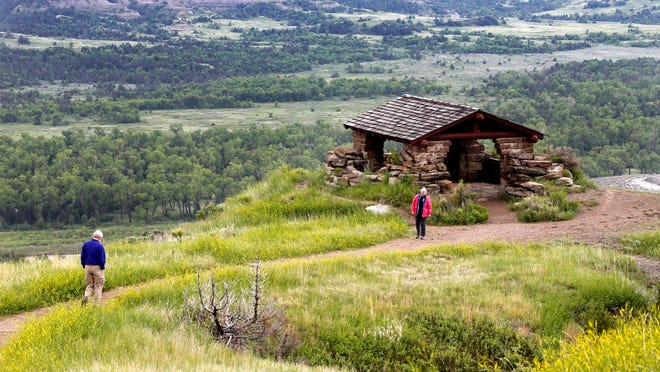 James Lyons and Florence Reaves, from Kirkwood, Mo., hike to a stone lookout inside Theodore Roosevelt National Park.