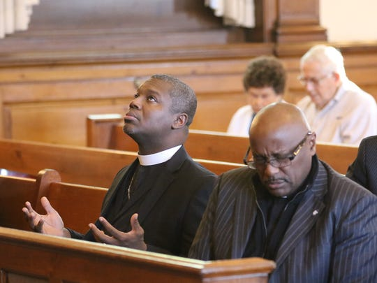 George Maize IV, left, pastor of Trinity Baptist Church in Hackensack, prays at a service on Wednesday for the victims of the shooting at the First Baptist Church of Sutherland Springs, Texas, last week.