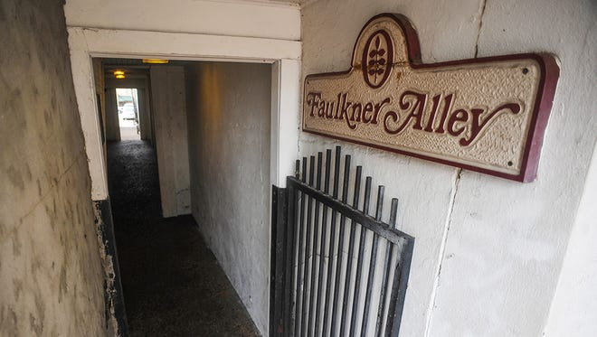 In this photo taken on Wednesday, July 8, 2015, a sign for Faulkner Alley, named after the famed Nobel Prize winning author William Faulkner, is displayed near the Square in Oxford, Miss. It is located between Southside Gallery and the Old Venice Pizza Company