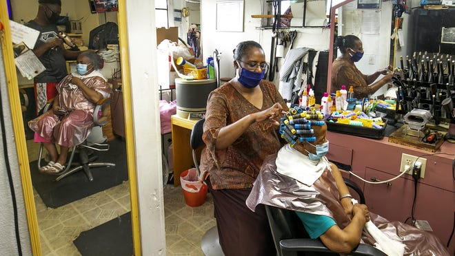 Tanya Hart works on a client's hair as her brother Gregory McCullough, shown in the mirror, blow-dries Hattie Williams' hair on July 31. Hart has owned J&T McCullough's Hair Salon, 1675 W. Silver Springs Blvd. in Ocala, since 1986. McCullough also works at the salon, washing hair and doing maintenance work at the building.
