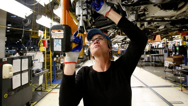Penny Snow, 47, of Charlotte, Michigan works at adding screws underneath a Chevrolet Traverse at the General Motors Lansing Delta Township Assembly Plant in Delta Township, Michigan on Thursday, January 16, 2020. GM said Tuesday it is investing $2 billion in six U.S. assembly plants