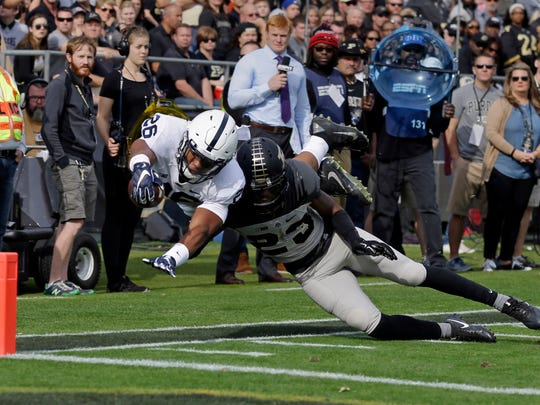 Penn State running back Saquon Barkley (26) dives short of the goal line as he's hit by Purdue cornerback Josh Hayes (23) during the first half of an NCAA college football game in West Lafayette, Ind., Saturday, Oct. 29, 2016.