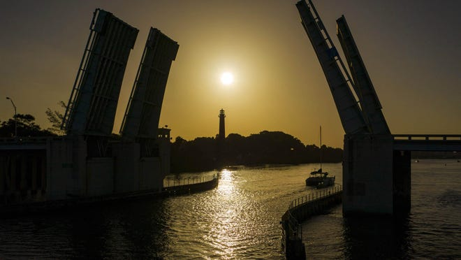 A boat passes under the U.S. 1 bridge as the sun rises in a hazy sky from Saharan dust on July 1 in Jupiter.