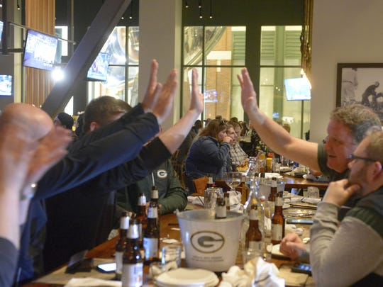 Fans at 1919 Kitchen & Tap trade high-fives on Thursday, April 26, after the Packers draft corner back Jaire Alexander of Louisville.