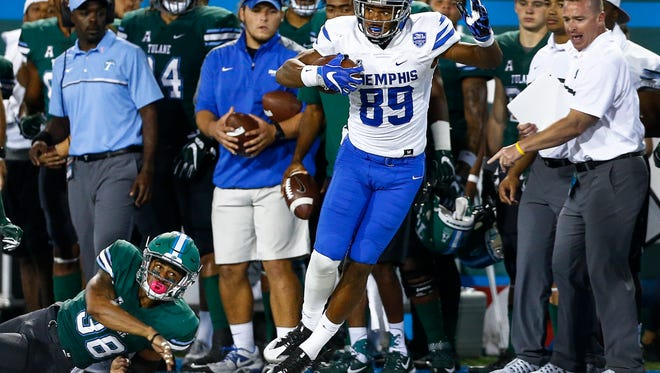 University of Memphis receiver Phil Mayhue (right) runs past Tulane University safety Roderic Teamer (left) after making a first down catch during third quarter action at Yulman Stadium in New Orleans.