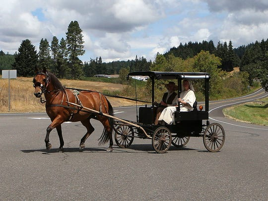 Eli and Cheryl Cutler drive their homemade buggy pulled by a horse named Whiskey across the highway near Lorane, Ore.