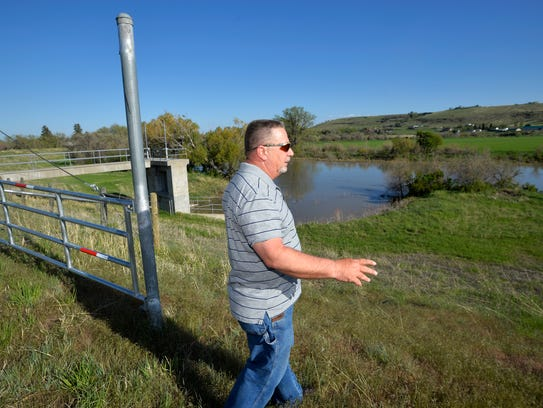 "Eric Bailey, president of the West Great Falls Flood and Drainage District, walks on the Sun River levee on the west side of Great Falls. ""The levee has performed as designed and built,"" he says."