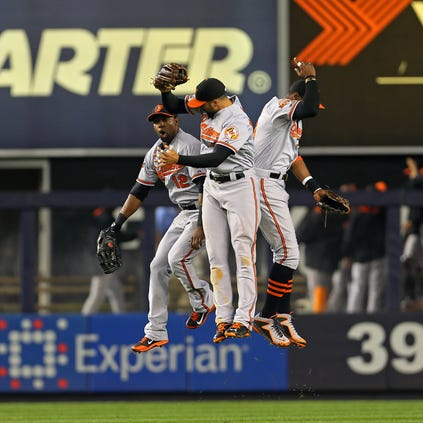 Sep 23, 2014; Bronx, NY, USA; Baltimore Orioles right fielder Nick Markakis (21), Steve Lombardozzi (12) and center fielder Adam Jones (10) celebrate their win against the New York Yankees at Yankee Stadium. The Orioles defeated the Yankees 5-4. Mandatory Credit: Adam Hunger-USA TODAY Sports