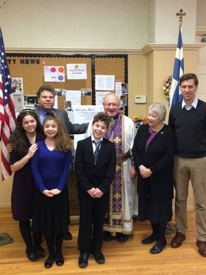 Front row from left, Rosalie and Amanda Hopko, and Alex Lambrou join, from left, Nick Lambrou (president of the parish council), Tom Parthenakis (pastor), Tompkins County Historian Carol Kammen and Alderman Seph Murtagh to commemorate the 196th anniversary of Greek Independence Day on Sunday at St. Catherine Greek Orthodox Church in Ithaca.