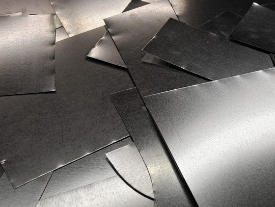 Pieces of cut sheet metal are laid out on the table