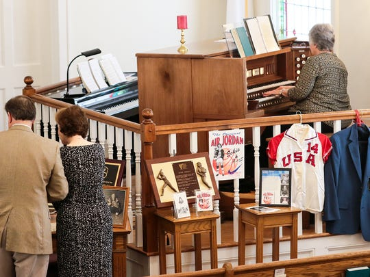 "A couple looks at items from Evelyn ""Eckie"" Juanita Jordan, while organist Gail Strickland, right, plays music, before the funeral for Jordan at First Baptist Church in Williamston on Tuesday."