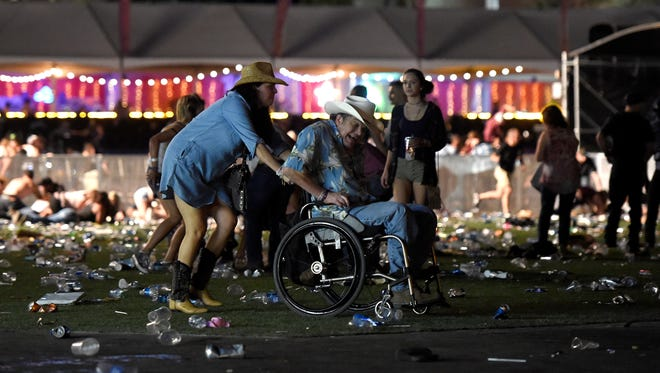 A man in a wheelchair is taken away from the Route 91 Harvest country music festival.