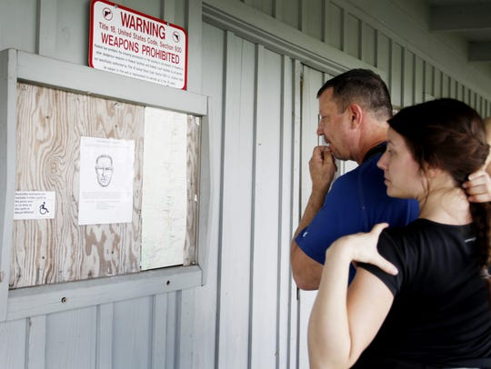 Dave Matthews, of Connecticut, looks at a bulletin board with his daughter, Kelsey, at the Craggy Gardens Visitor Center on the Blue Ridge Parkway in 2016. Posted on the board is a sketch of a man suspected in sexually assaulting a hiker not far from the Craggy Gardens trail.