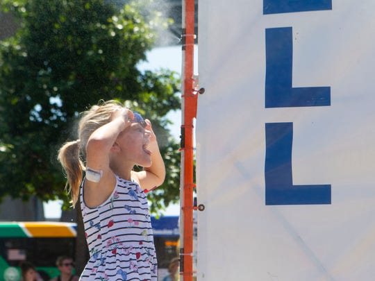 Johanna Zwaska, 8, cools off in front of a misting station at Summerfest on Friday. The heat index exceeded 100.
