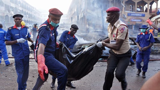 Rescue workers carry the remains of a person in a body bag  after a explosion at a shopping mall in Abuja, Nigeria.
