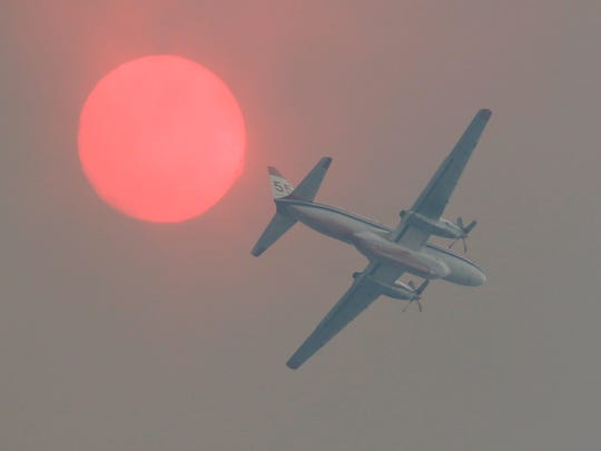 A firefighting airplane passes near the sun turned