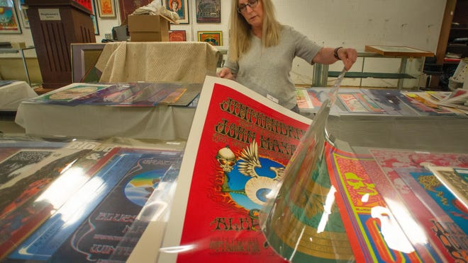 Cindy Stephenson looks through some of the 300-plus concert posters in the showroom while setting up for the auction of the Perry Pfeffer estate's collection of rock concert posters Tuesday at Stephenson's Auctioneers and Appraisers in Upper Southampton.
