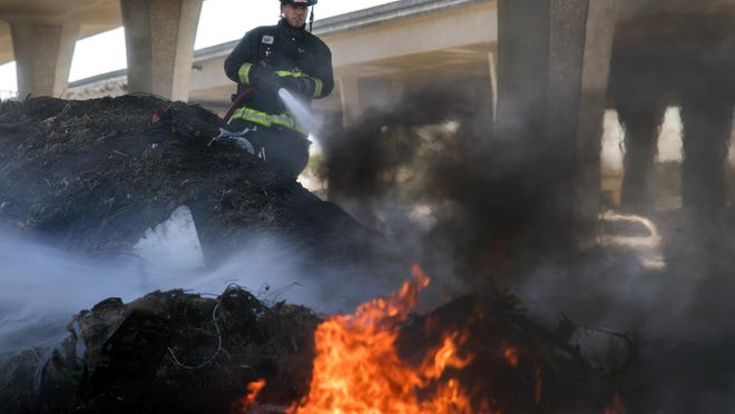 A Stockton firefighter battles a debris pile fire in the Caltrans yard under the Crosstown Freeway along Washington Street near Grant Street in downtown Stockton on Sunday.