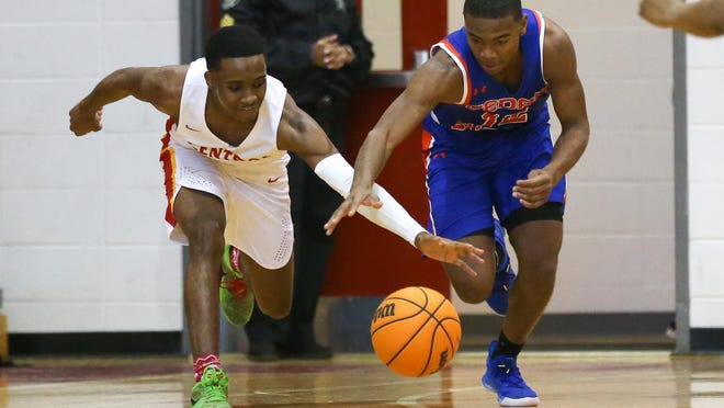 Cedar Shoals Jaiden Williams (12) and Clarke Central's Jaiquez Smith (2) compete for a loose ball during a game last season between Clarke Central and Cedar Shoals. The Jaguars won 66-56.