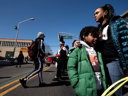 Takia Davis hugs her cousin Damoni Robertson, 6, during CeaseFire Paterson's annual prayer march. Davis' son Kasir Davis was shot and killed on Auburn Street when he was 16.