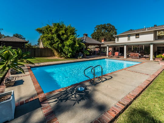 The backyard includes an outdoor kitchen area plus a huge pool.