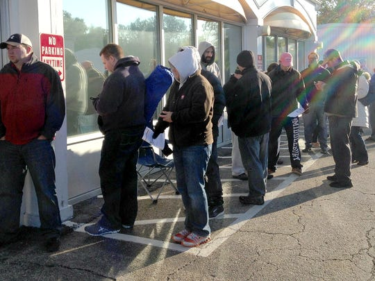 People wait outside the AT&T store on Dorset Street in South Burlington Friday morning.