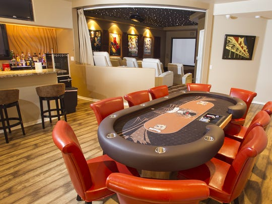 The basement poker table, bar and theater area in the