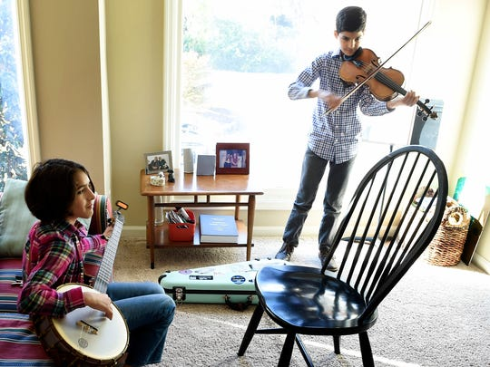 Uma and Giri Peters practice their instruments at their