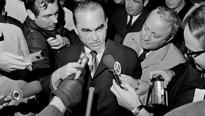 "In this Oct. 29, 1968 file photo, reporters surround presidential candidate, former Alabama Gov. George Wallace at Metro Airport in Detroit, Mich., after the presidential candidate arrived to address a night rally at Cobo Hall. Donald Trump promises to ""Make America Great Again."" George Wallace said he would ""Stand up for America."" The 2016 Republican presidential front-runner doesn't say he's following the 1960s playbook of the Alabama segregationist, a four-time presidential hopeful. (AP Photo/Preston Stroup)"