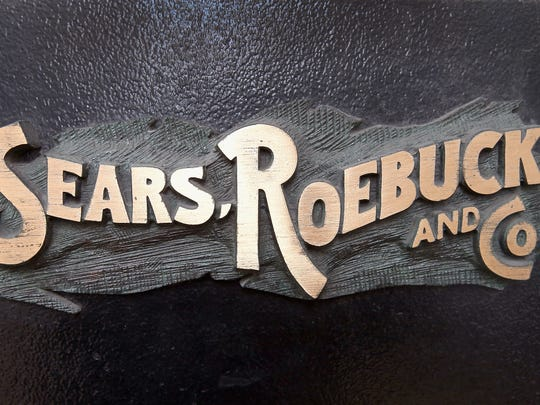 A bronze plaque hangs near the entrance of Sears' flagship