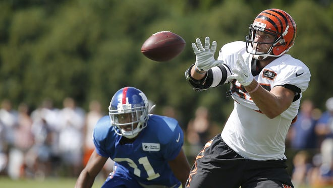 Bengals tight end Tyler Eifert catches a pass as Giants defensive back Trevin Wade defends during joint 11-on-11 drills at training camp on Aug. 12, 2015.