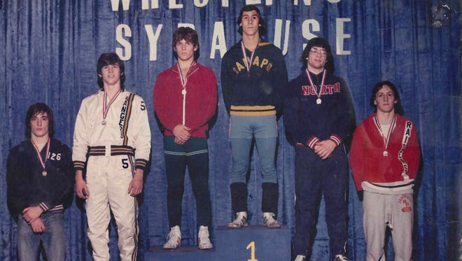 Steve Silverberg stands atop the podium at the 1975 New York state wrestling championships.
