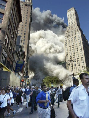 Pedestrians flee the area of the World Trade Center as the center's south tower collapses following a terrorist attack on the New York landmark on Sept. 11, 2001.