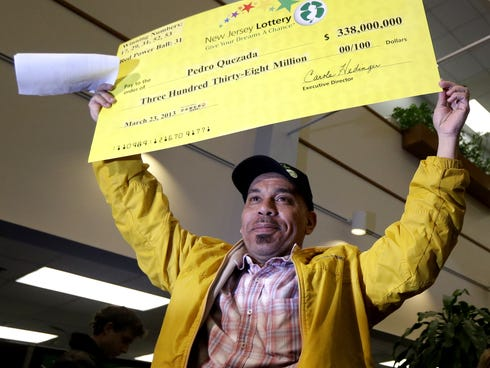 Pedro Quezada, the winner of the Powerball jackpot, holds up a promotional check during a news conference at the New Jersey Lottery headquarters, March 26, 2013, in Lawrenceville, N.J.