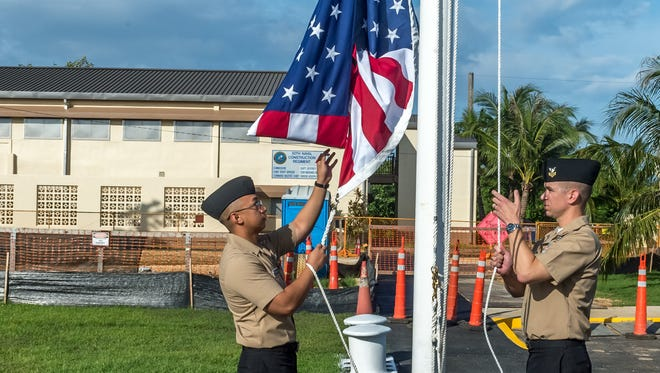 Yeoman 1st Class Travis Aquino, left, and Equipment Operator 1st Class Clinton Burch raise the American flag over the 30th Naval Construction Regiment headquarters, officially marking its relocation to Guam from Port Hueneme, California on July 1, 2018. This move streamlines operational effectiveness and establishes the regiment as a forward-deployed operational staff capable of commanding and controlling Naval Construction Force units deployed to the 7th Fleet area of operations.