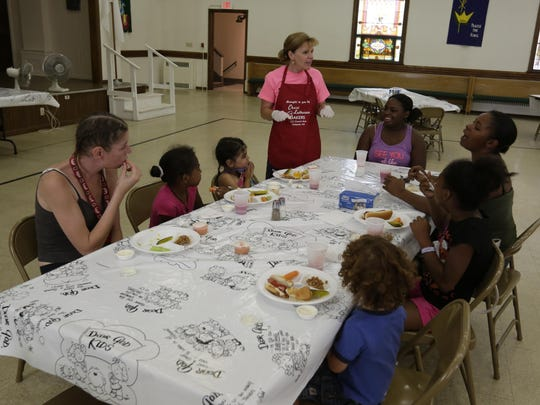 Mary Backus of Christ Lutheran Church comes out to talk to the two families that came to the lunchtime meal at the church. Christ Lutheran Church is serving a free lunch to families from 11 a.m. to 1 p.m. They are filling the gap where the Oshkosh Area School District left off by serving families until school begins in September.