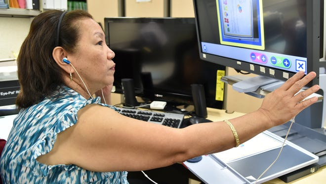 Clerical worker Mary Pineda demonstrates the use of her closed-circuit television (CCTV) text reader, at Naval Hospital Guam in Agana Heights on Oct. 12. The assistive technology scans documents, and reads them aloud for Pineda to process.