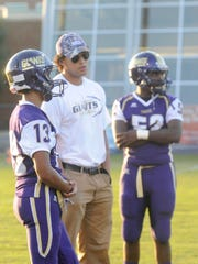 Waynesboro assistant coach Jacobie Napie, a 2001 graduate of Waynesboro, speaks with Little Giants wing back Steffan Thornton before the team's game against Spotswood on Friday.
