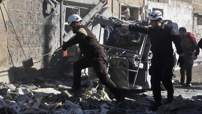 This photo released on Feb. 18, 2019, by the Syrian Civil Defense group shows White Helmet civil defense workers in a street hit by a shell from Syrian forces, in the town of Maaret al-Numan, Idlib, north Syria.
