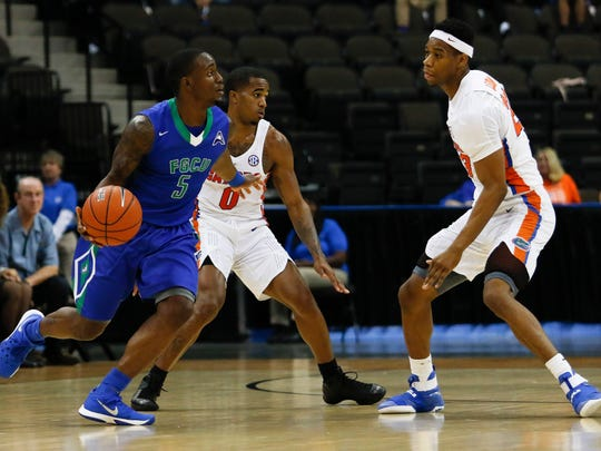 Florida Gulf Coast Eagles guard Zach Johnson (5) dribbles the ball in the second half as Florida Gators forward Justin Leon (23) defends at Jacksonville Veterans Memorial Arena. Florida Gators won 80-59 on Nov. 11, 2016, in Jacksonville.