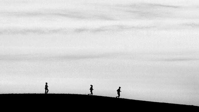 Runners move along a hill in Mayhew Creek Park in Sauk Rapids, the site of this Tuesday's Walk in the Park. The walk begins at noon.